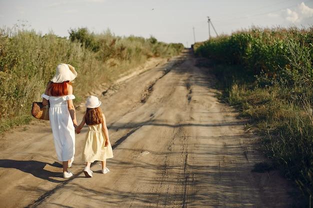 Mutter mit der tochter, die auf einem sommergebiet spielt