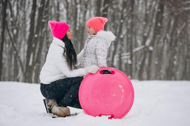 Mutter mit der tochter, die auf platte im winterpark fährt
