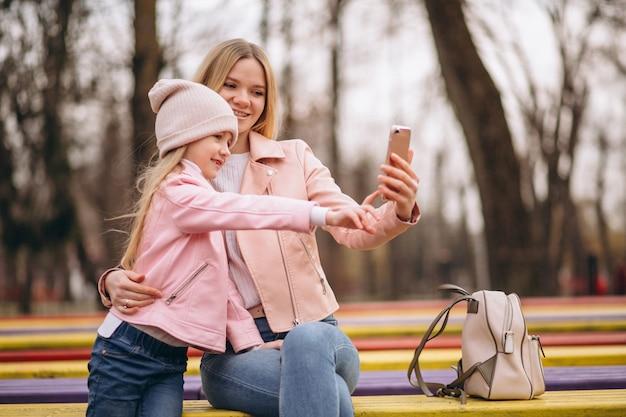 Mutter mit der tochter, die draußen im park selfie macht