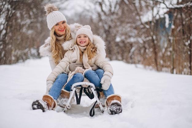 Mutter mit der tochter, die draußen im winter sledging ist