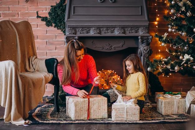 Mutter mit der tochter, die geschenk durch kamin auf weihnachten verpackt