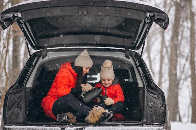 Mutter mit der tochter, die im auto im winter sitzt