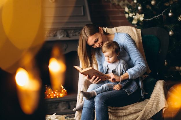 Mutter mit der tochter, die im stuhl durch weihnachtsbaum sitzt