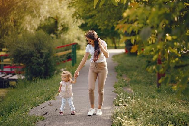 Mutter mit der tochter, die in einem sommerpark spielt