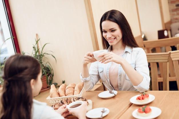 Mutter mit der tochter, die kuchen in der cafeteria isst.