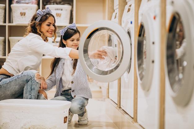 Mutter mit der tochter, die wäscherei am waschsalon der selbstbedienung tut