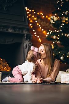 Mutter mit der tochter, die weihnachtsgeschenke durch weihnachtsbaum auspackt