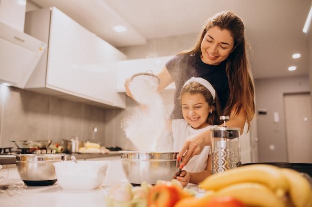 Mutter mit der tochter, die zusammen an der küche backt