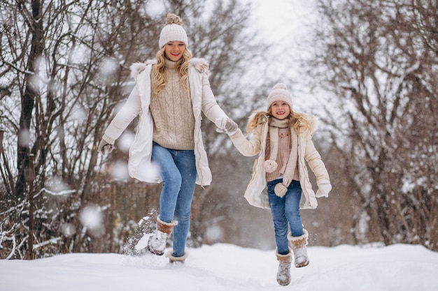 Mutter mit der tochter, die zusammen in einen winterpark geht