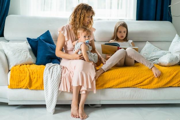 Mutter mit drei kindern, die in gemütlicher atmosphäre ein buch lesen