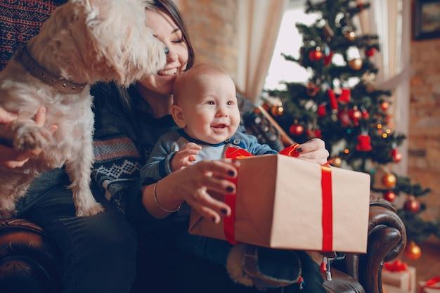 Mutter mit einem baby auf dem arm und dies mit einem geschenk