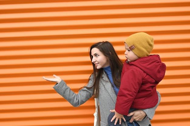 Mutter mit einem baby in der hand streckt ihre handfläche aus und zeigt auf etwas