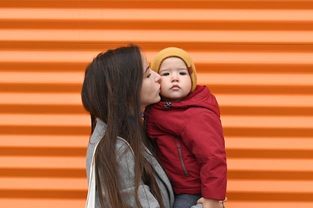 Mutter mit einem baby in ihren armen in warmen kleidern, auf einem orangefarbenen hintergrund.