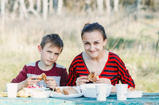 Mutter mit einem kind, das fleisch auf der natur im wald isst
