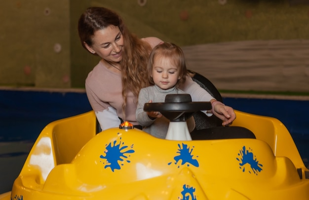 Mutter mit einem kleinen mädchen fahren ein boot im pool. zeit teilen im kinderunterhaltungszentrum. familienurlaub