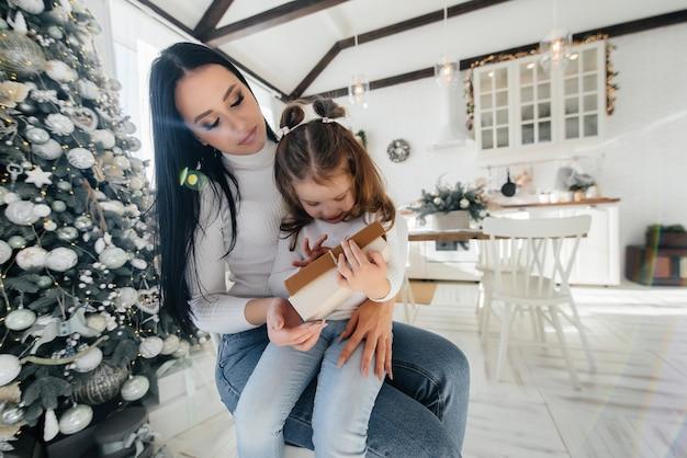Mutter mit einem kleinen mädchen packen geschenke aus. urlaub.