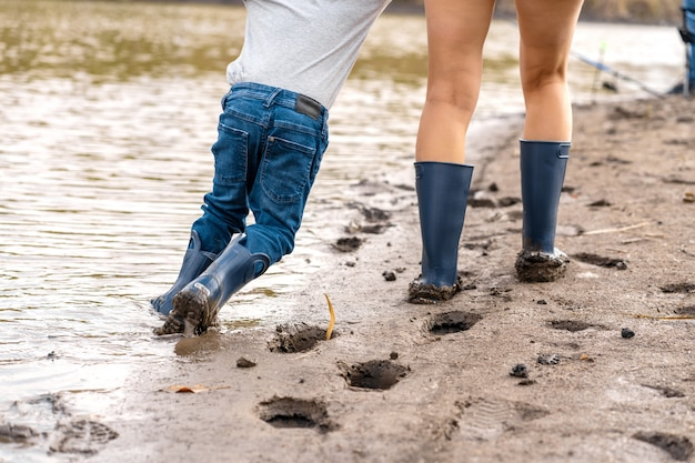 Mutter mit einem kleinen sohn geht mit gummistiefeln am sandigen seeufer entlang.