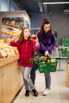 Mutter mit einer tochter in einem supermarkt