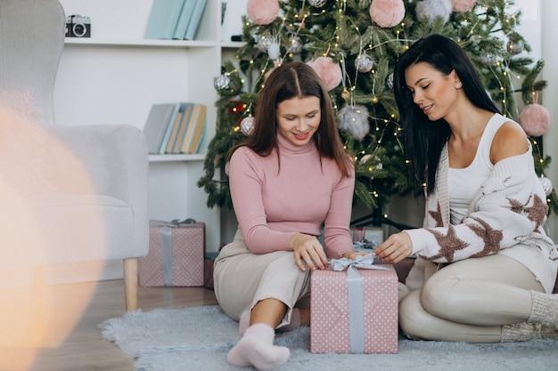 Mutter mit erwachsener tochter mit weihnachtsgeschenken durch weihnachtsbaum