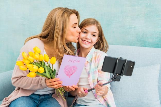 Mutter mit geschenken die tochter küssend, die selfie nimmt
