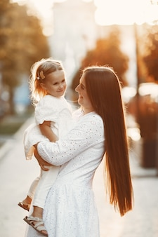 Mutter mit heiterem spiel. frau in einem weißen kleid. familie auf einem sonnenunterganghintergrund.