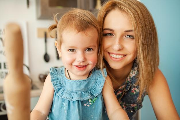 Mutter mit ihrem 2-jährigen kind, das feiertagstorte in der küche zum muttertag kocht