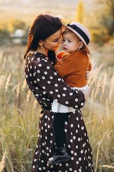 Mutter mit ihrem baby auf einem herbstgebiet