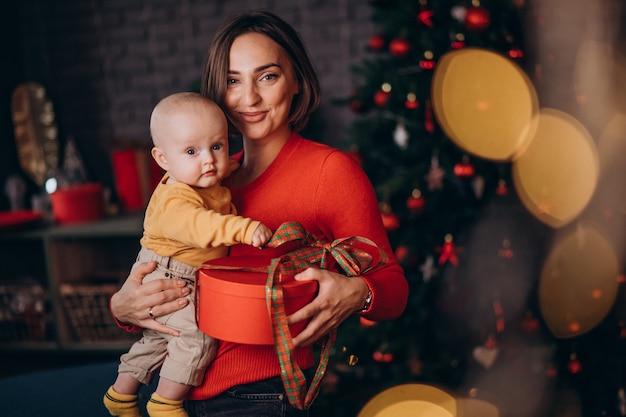 Mutter mit ihrem baby, das weihnachten feiert