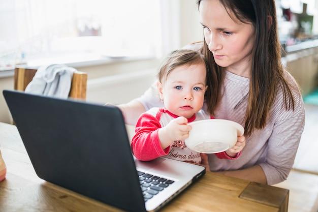 Mutter mit ihrem baby unter verwendung des laptops