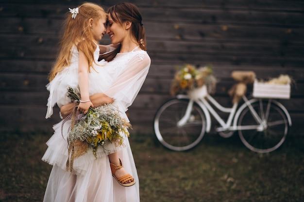 Mutter mit ihrem kind in schönen kleidern mit fahrrad