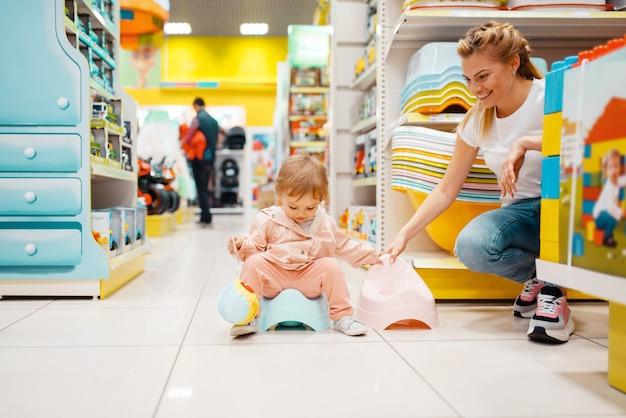 Mutter mit ihrem kleinen mädchen, das babytöpfchen im kindergeschäft wählt.