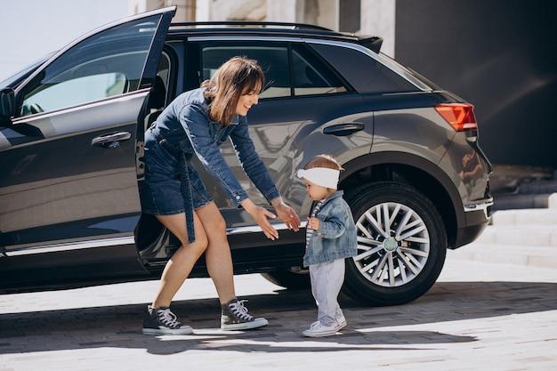 Mutter mit ihrem kleinen mädchen, das spaß mit dem auto hat, das in der nähe ihres hauses geparkt ist