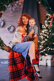 Mutter mit ihrem kleinen sohn am weihnachtsbaum