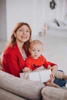 Mutter mit ihrem kleinen sohn, der auf sofa sitzt und weihnachtsgeschenke auspackt