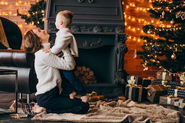 Mutter mit ihrem kleinen sohn, der durch weihnachtsbaum sitzt