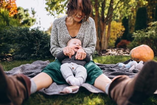 Mutter mit ihrem kleinen sohn, der picknick auf einem hinterhof hat