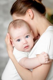 Mutter mit ihrem neugeborenen. mutter hält ihr kleines baby. foto mit der wirkung des sonnenlichts, weiches natürliches licht, mit selektivem fokus. baby auf mamas schulter.