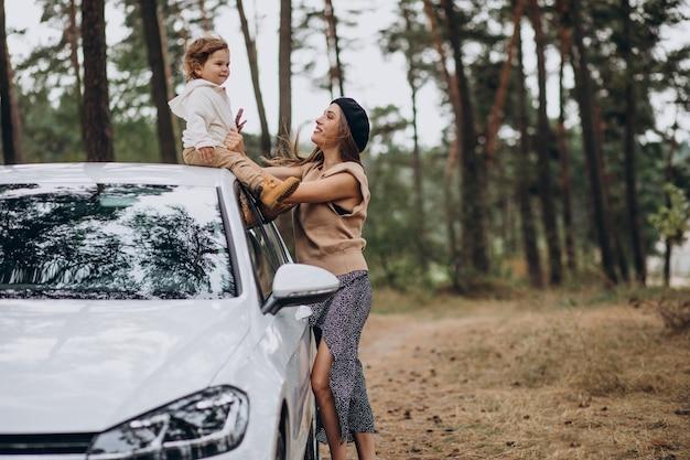 Mutter mit ihrem sohn am auto im park