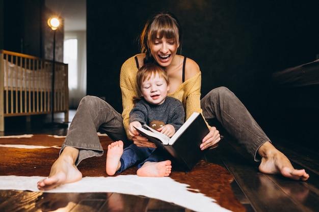 Mutter mit ihrem sohn, der lesebuch spielt