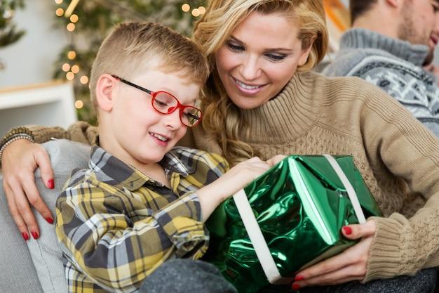 Mutter mit ihrem sohn und einem großen grünen geschenk