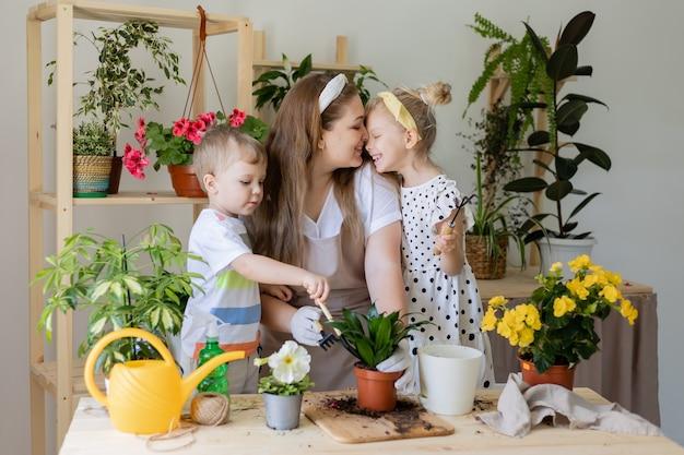 Mutter mit ihrem sohn und ihrer tochter in der fastenpflanze oder verpflanzt zimmerblumen, die zimmerpflanzen pflegen