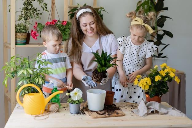 Mutter mit ihrem sohn und ihrer tochter in der fastenpflanze oder verpflanzt zimmerblumen
