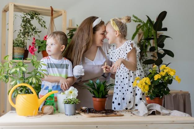 Mutter mit ihrem sohn und ihrer tochter in fastenpflanze oder transplantation von indoor-blumen-lifestyle