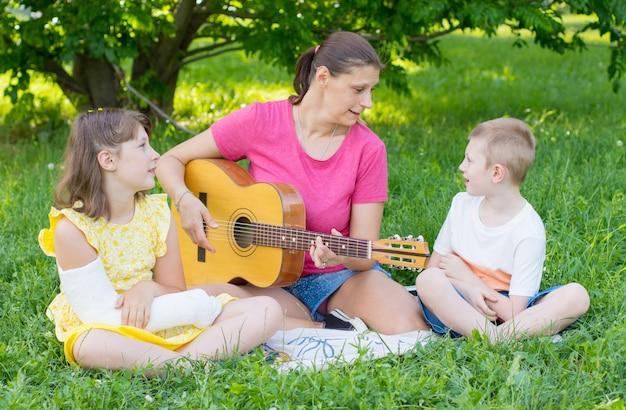 Mutter mit ihren beiden kindern spielt gitarre im park.