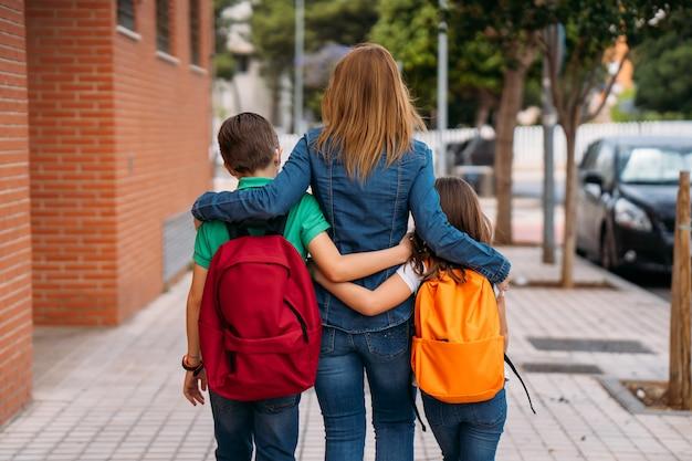 Mutter mit ihren kindern geht mit masken bei coronavirus-pandemie zur schule
