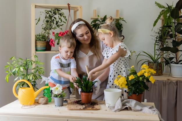 Mutter mit ihren kindern in der fastenpflanze oder verpflanzt zimmerblumen kleiner helfer bei der hausarbeit