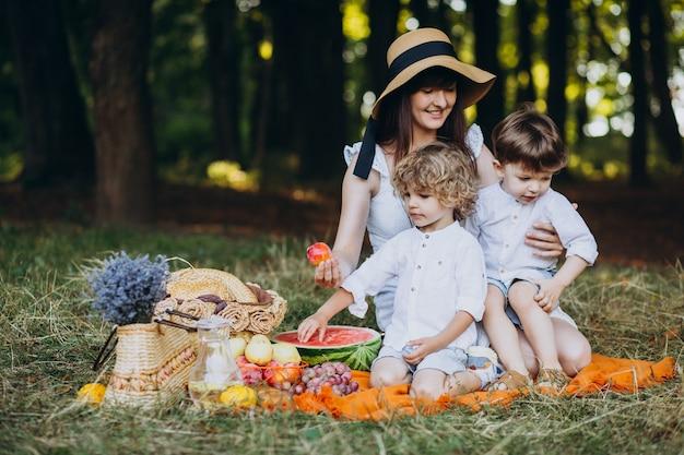 Mutter mit ihren söhnen beim picknick im wald