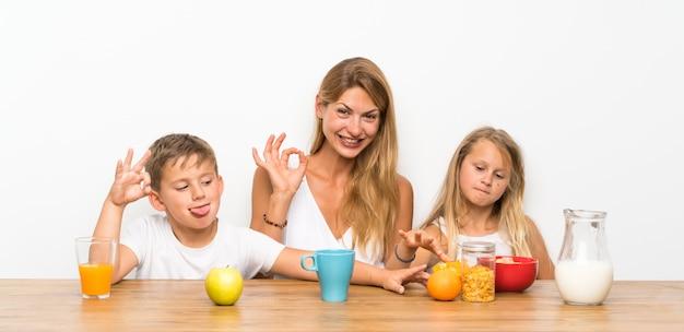 Mutter mit ihren zwei kindern, die frühstücken und okayzeichen bilden