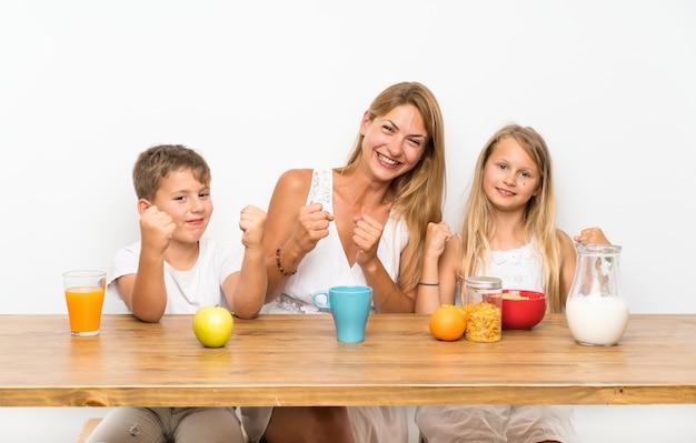Mutter mit ihren zwei kindern, die frühstücken und sieggeste machen