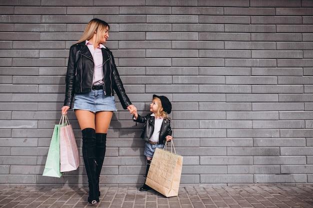 Mutter mit ihrer kleinen süßen tochter mit einkaufstüten